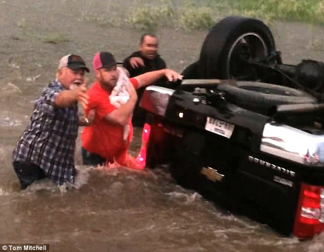 The rescuer struggled against the fast moving water with the baby balanced in his arms