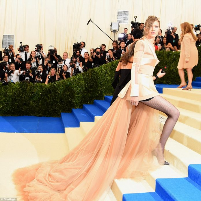 Fun with fashion: Gigi struts up the stairs in her asymmetrical Tommy Hilfiger gown which boasted a dramatic train