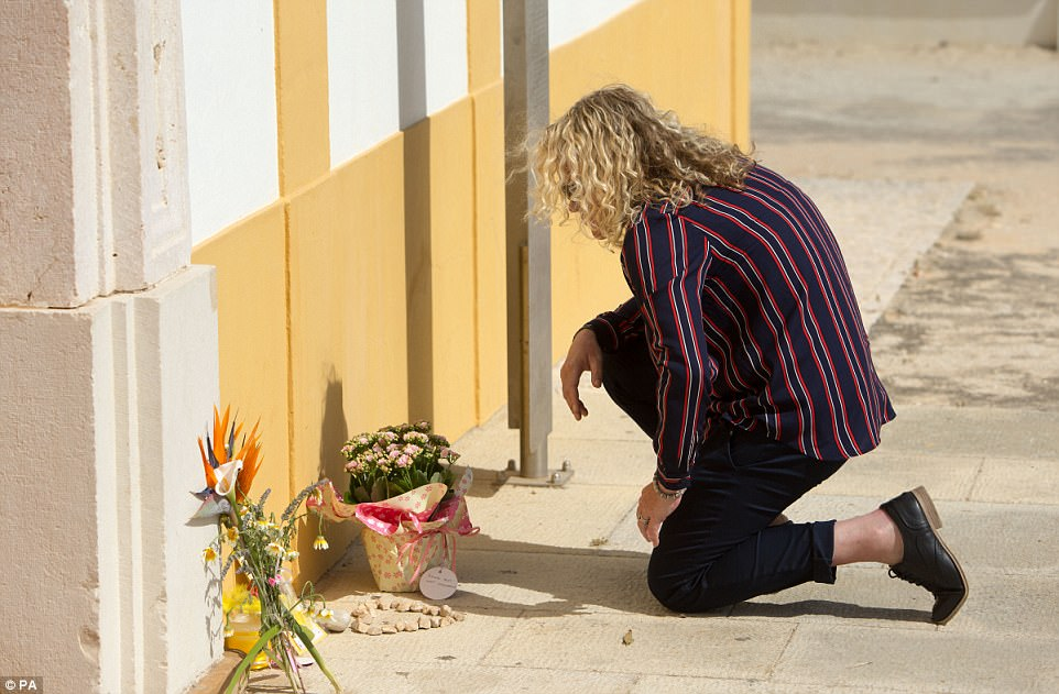 Ronay Crompton, 38, from Bradford, leaves a tribute to Madeleine McCann outside the Church of Nossa Senhora da Luz in Praia Da Luz, where the child went missing from ten years ago