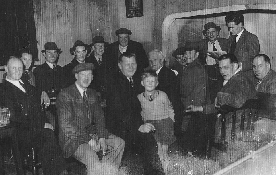 A picture taken in the mid-20th century shows a group of men, and a young boy, sharing a drink beneath the enormous stone fireplace, that is one of the striking features of the pub