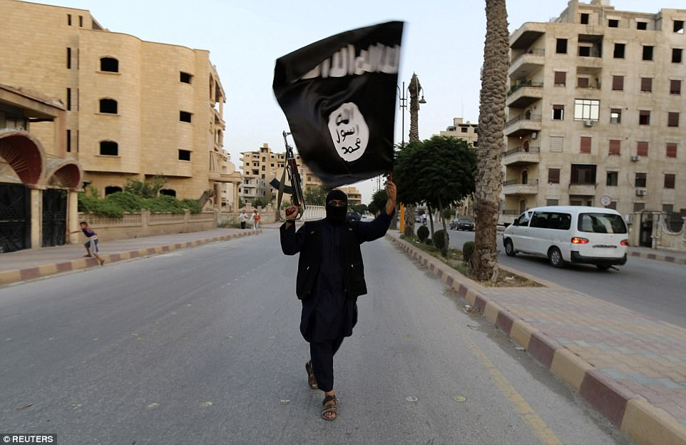 A member of ISIS is seen waving the flag of the terror group while holding a gun in Raqqa, Syria (file photograph). Four attacks have taken place in Raqqa so far this year, which led to five people being killed
