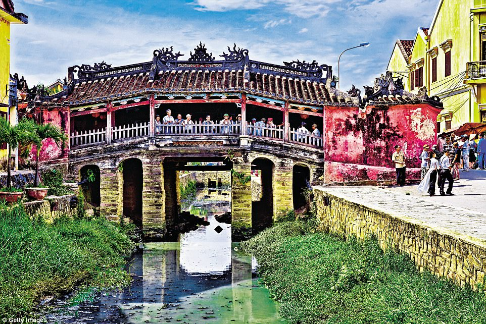 Charming: People gather on a beautifully ornate and colourful bridge in Hoi An