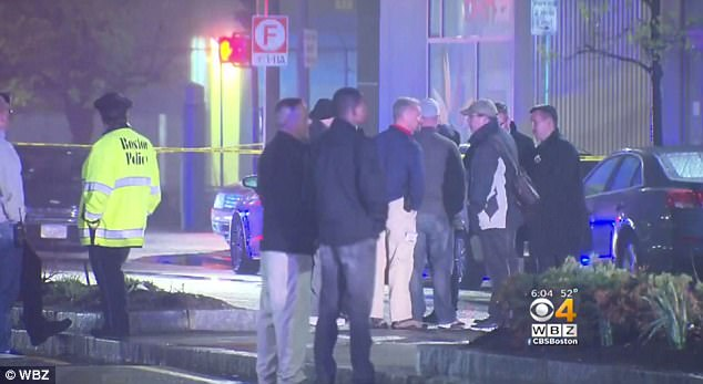 People are pictured gathered outside the doctors' luxury apartment building in South Boston