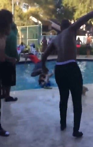 The man (pictured in red) falls into the swimming pool after throwing the woman in