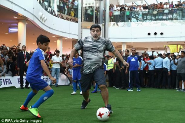 Maradona enjoys a game of football with some children at a shopping centre in Manama