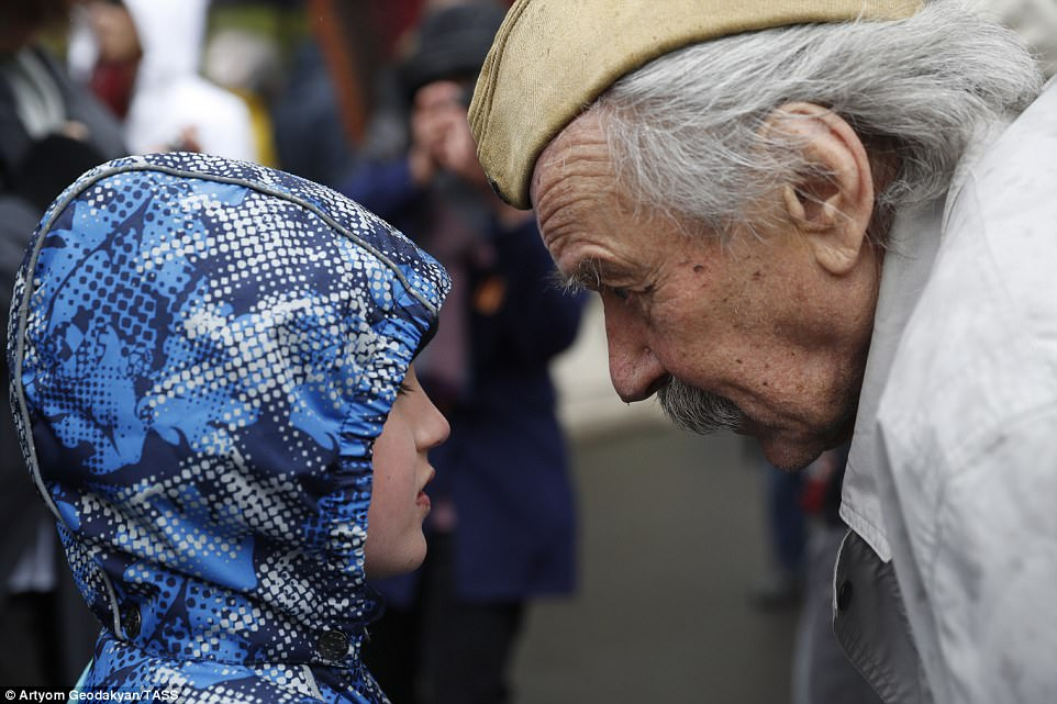 World War Two veteran Vladimir Ivanov talks to a child during celebrations in Gorky Park marking the 72nd anniversary of the Victory over Nazi Germany