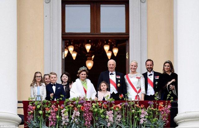 Leah Isadora Behn, Princess Ingrid Alexandra, Prince Sverre Magnus, Maud Angelica Behn, Queen Sonja, Emma Tallulah Behn, King Harald, Crown Princess Mette-Marit, Crown Prince Haakon and Martha smile at the well wishers below