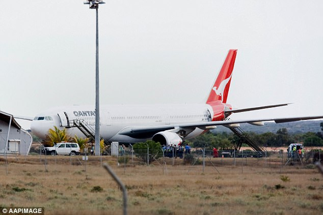 The Airbus A330 sits on the ground as emergency crews attend to it after an emergency landing in Learmonth, Western Australia
