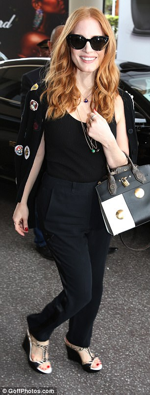 Stunning: She flashed a peep of her scarlet pedicure in monochrome wedges and wore a selection of thin necklaces