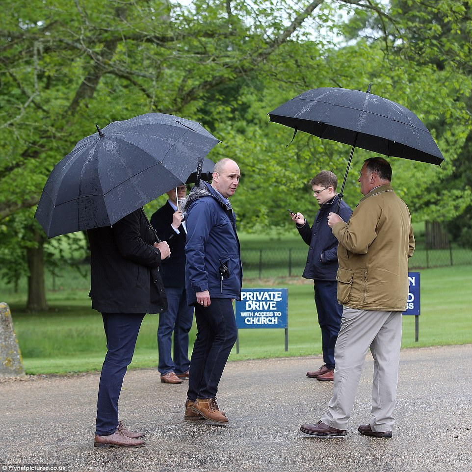A team of men chatted outside in the rain as the village gears up for the biggest event in its history this weekend
