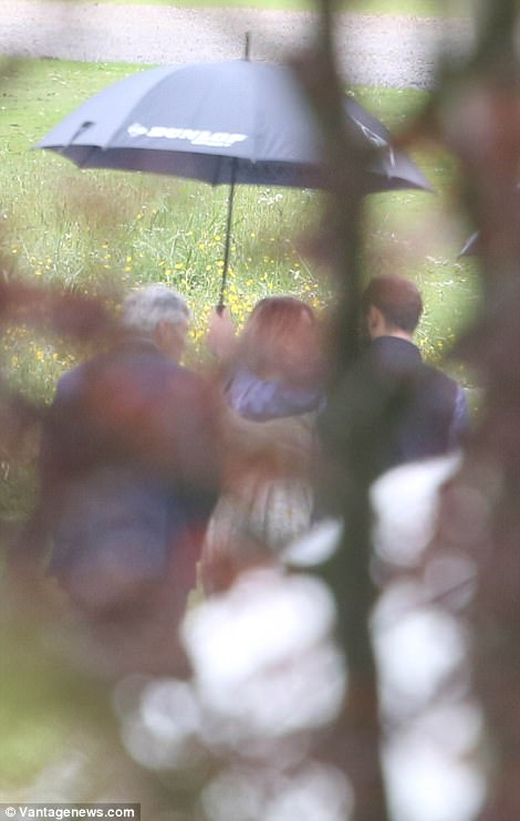 Michael, Carole and James Middleton, left, sheltered under an umbrella