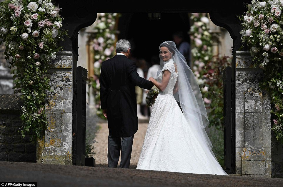 The 33-year-old beamed with happiness as she displayed her famous figure in the fitted guipure lace gown by Giles Deacon as she arrived with her father Michael at St Mark's Church