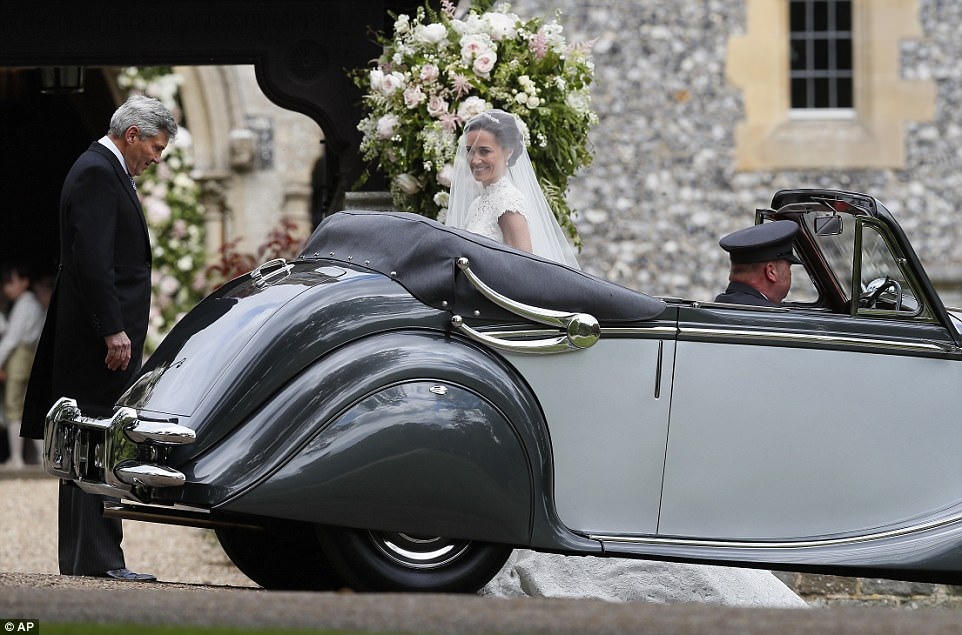 Pippa beamed with joy whilst her father admired her dress when the pair arrived at the wedding in aJaguar Mark V