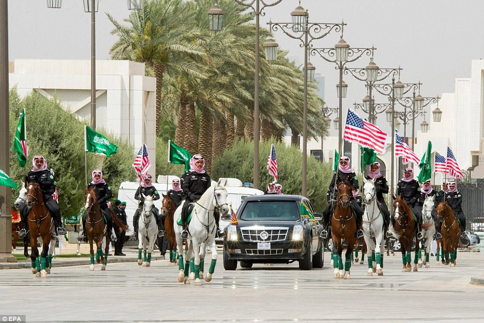 Soldiers on horseback carry US and Saudi Arabia flags and escort a car carrying Donald Trump to the Saudi Royal Court