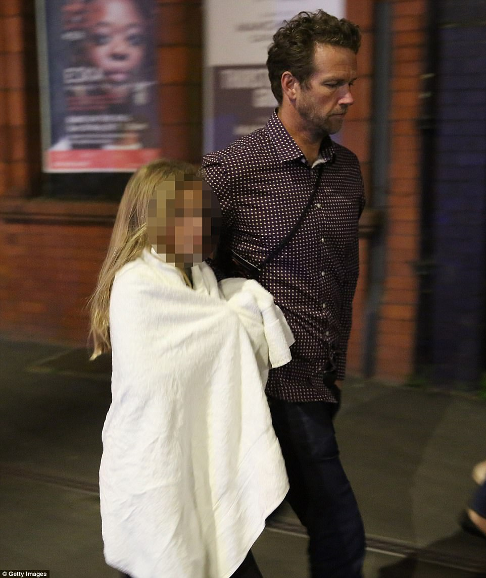 A man comforts a child wrapped in a white blanket. Lots of other children were seen being cared for by police and passers-by