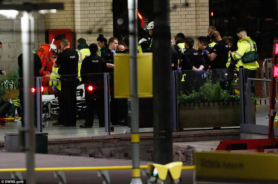 """There were reports that a Holiday Inn hotel near Manchester Arena had taken in """"50+ children"""" who were unaccompanied at the gig. Pictured: Paramedics, watched by police, help casualties"""