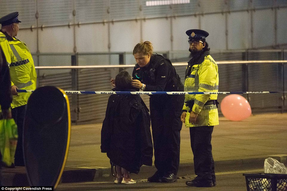 A young girl is helped by police after the horrific incident inside the teen concert this evening