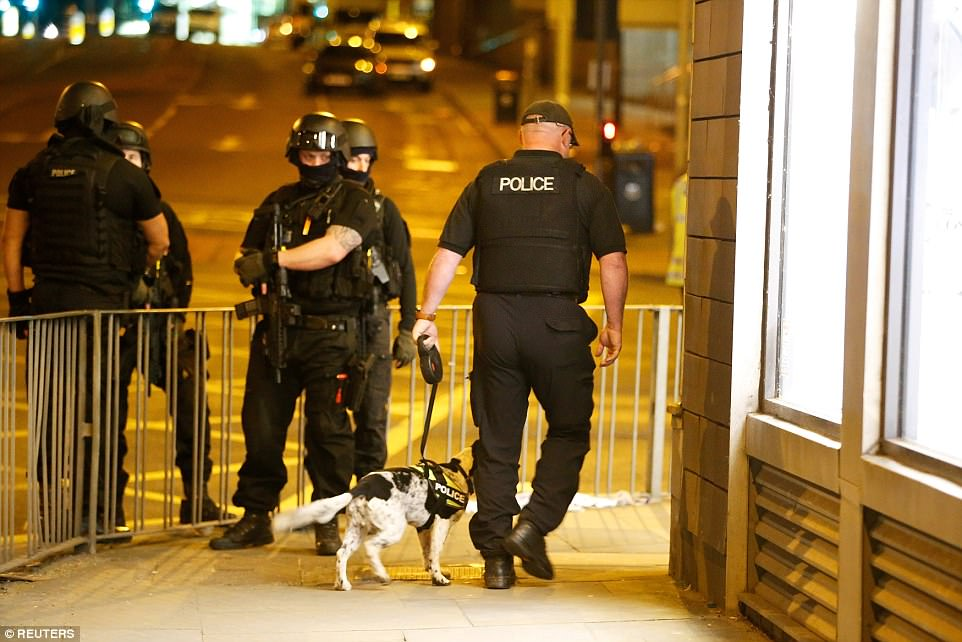 Heavily-armed officers watch on as a colleague with a dog walks along the pavement.Greater Manchester Police say they are working with intelligence agencies to investigate the attack