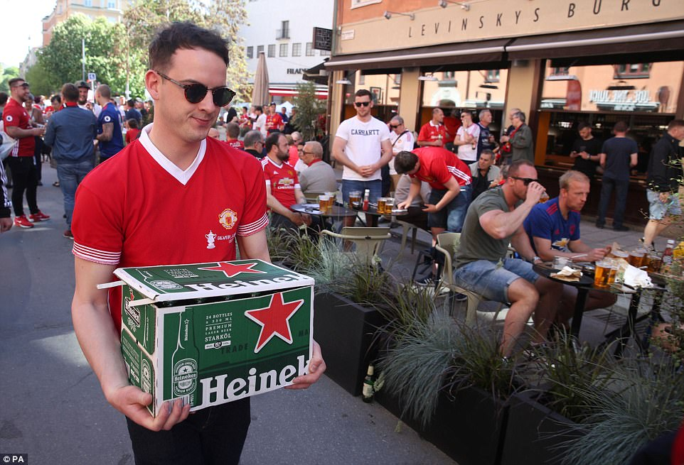 A United fan carries a crate of beer in the city centre on a hot afternoon in Sweden