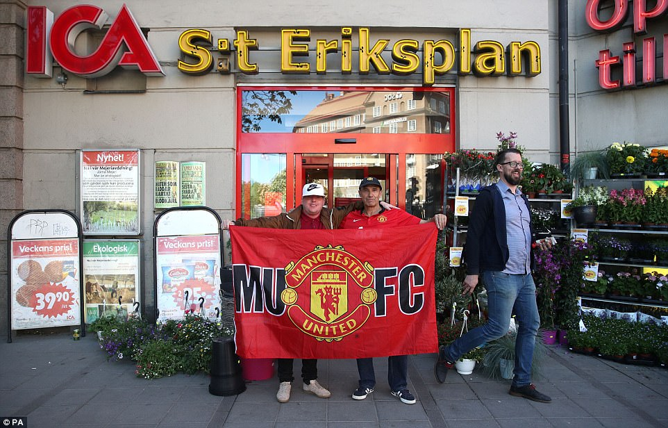 United fans pose with another banner in the centre of Stockholm on Wednesday afternoon
