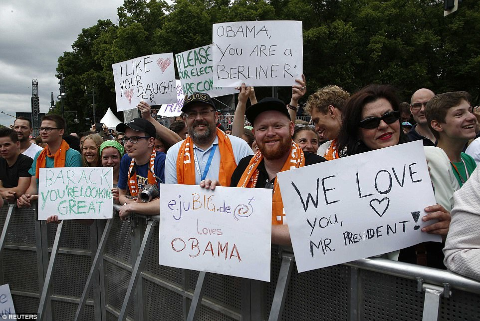 Germans hold signs as they attend an event that attracted former President Obama, who sat alongside German Chancellor Angela Merkel