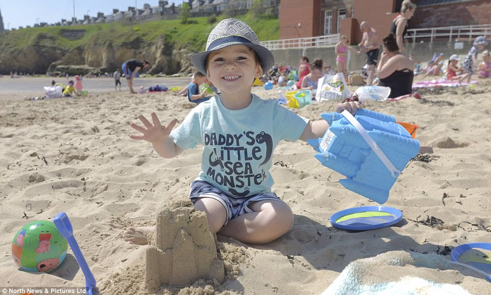 Youngster James Botan, 3, has fun building sandcastles at Cullercoats Bay in North Tyneside as the continuted spell of sunshine sees crowds flock to the beach