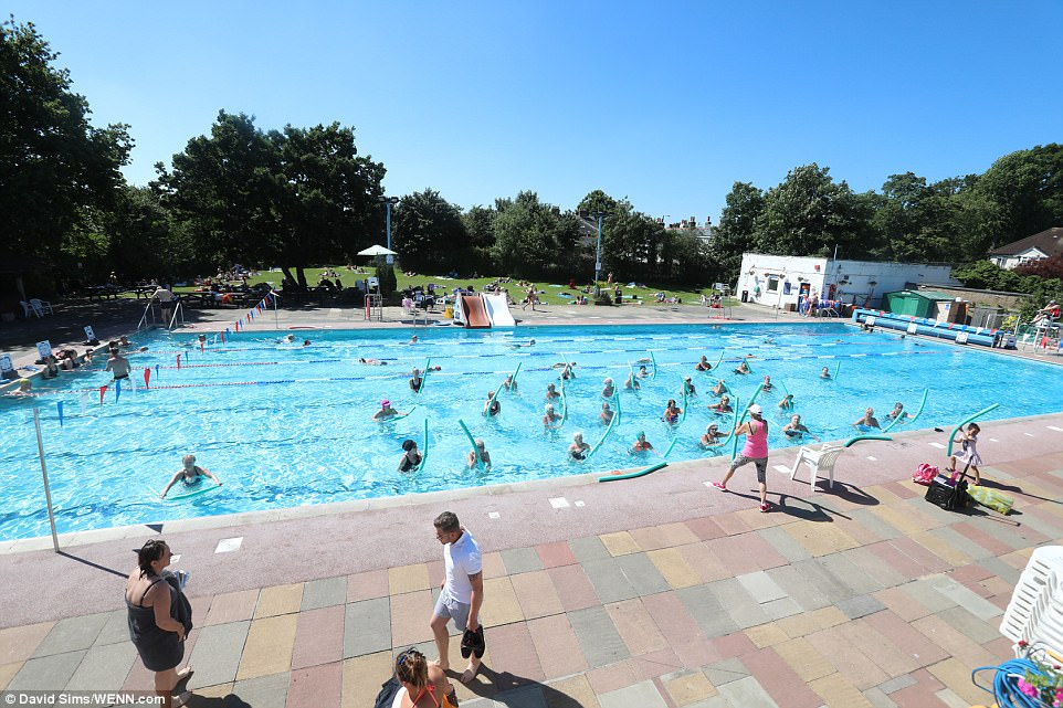Bathers enjoy the hottest day of the year at Hampton pool in Hampton, Surrey, on Friday as the country warms up for the bank holiday weekend