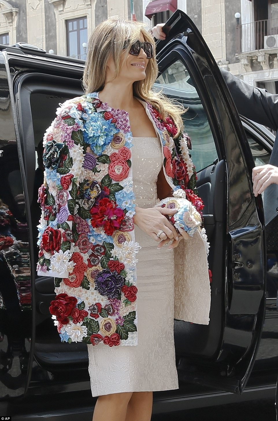 Melania's form-fitting Dolce & Gabbana dress matches the lining of her statement coat, which she wore over her shoulders