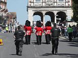 Defiant: Jubilant children gazed from their parents' shoulders as tourists took selfies under the blue skies of the year's hottest day so far at the Changing of the Guard