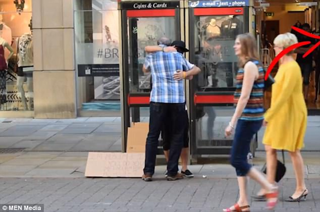 The video shows him hugging one man who stopped after he read his sign in the centre of Manchester