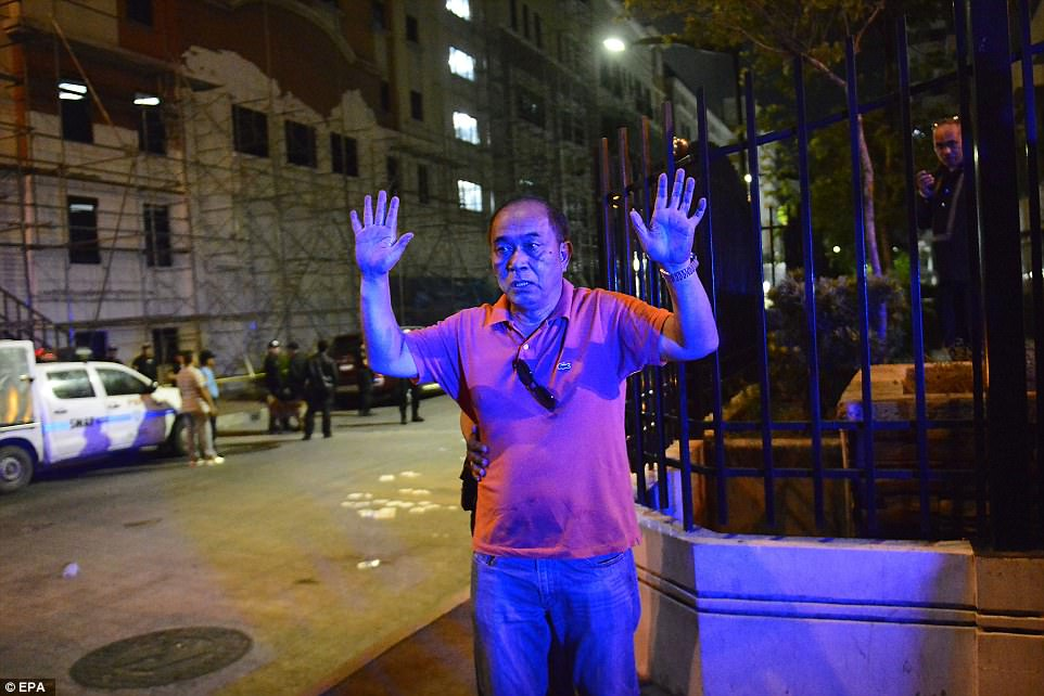 A Filipino man is pictured raising his hands to police outside the Resort World Manila hotel in Pasay city, Manila