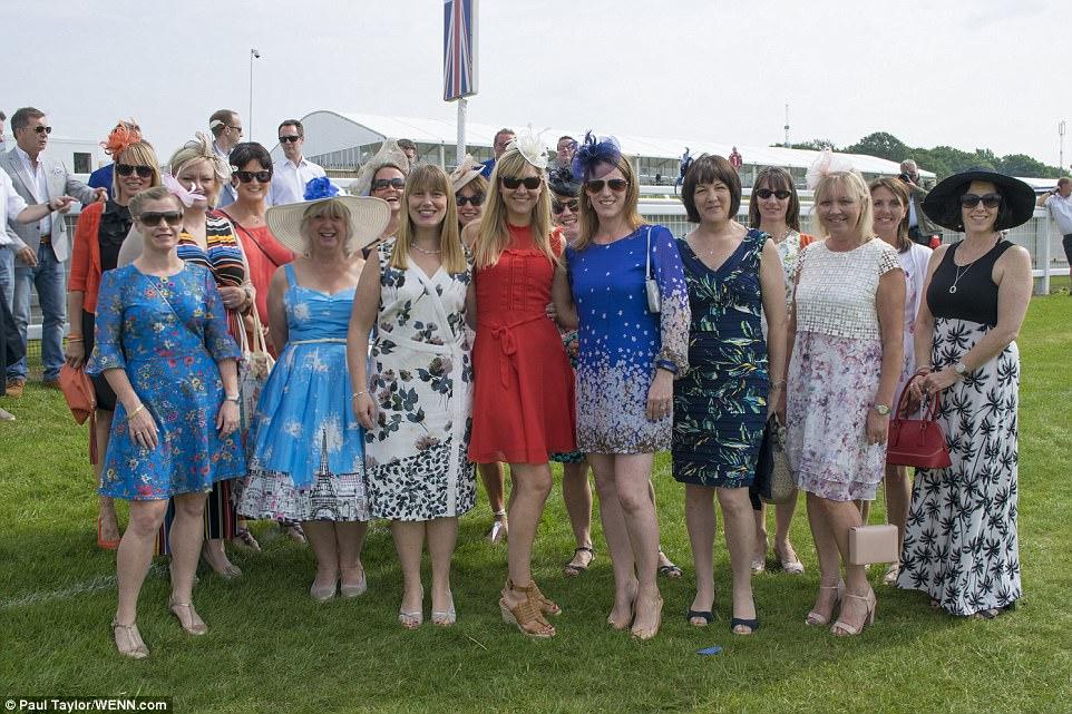 De bom humor: um grupo de senhoras colocou para as câmeras em seus melhores vestidos enquanto eles se preparavam para um dia divertido no sol no evento glamouroso em Surrey