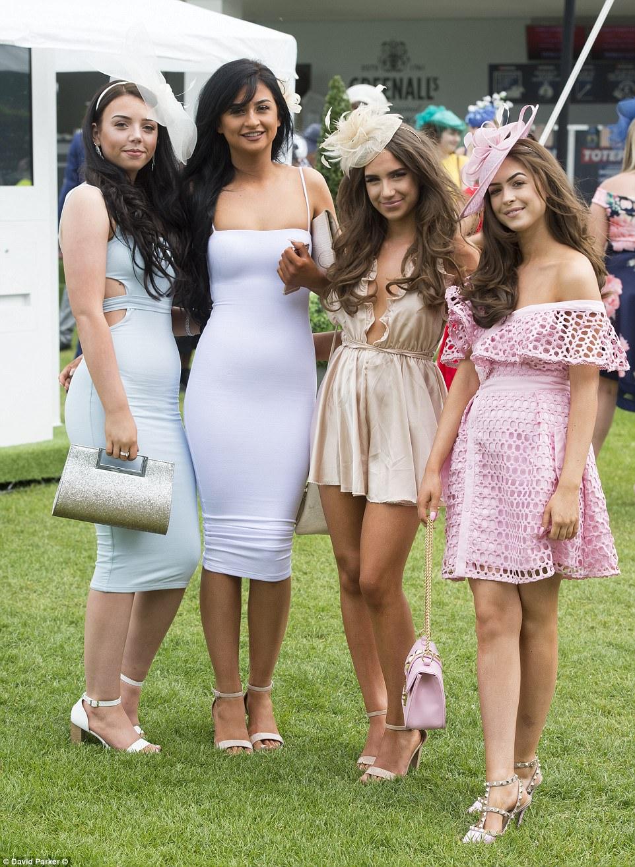 Quanto mais apertado, melhor!  Um grupo de mulheres glamourosas vestiu-se de vestidos de figurinhas e vestidos de cetim de baixo corte para o dia nas corridas