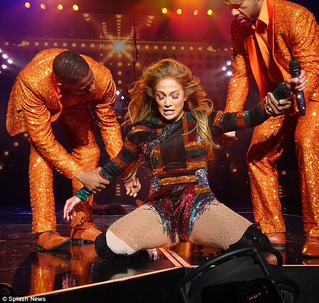 You okay? The look of concern on the faces of her dancers - clad in sparkling orange sequinned suits - was unmistakable as they grabbed an arm each