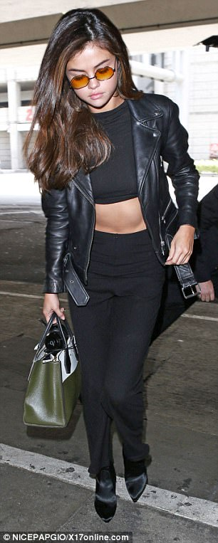 Off duty pop star: A cropped top and matching trousers, worn beneath a leather jacket, highlighted her slender waist
