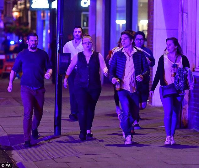 material de archivo de la aterradora escena muestra a los agentes de policía gritando 'Borrar la escena ahora!' peatones como de pánico huyen