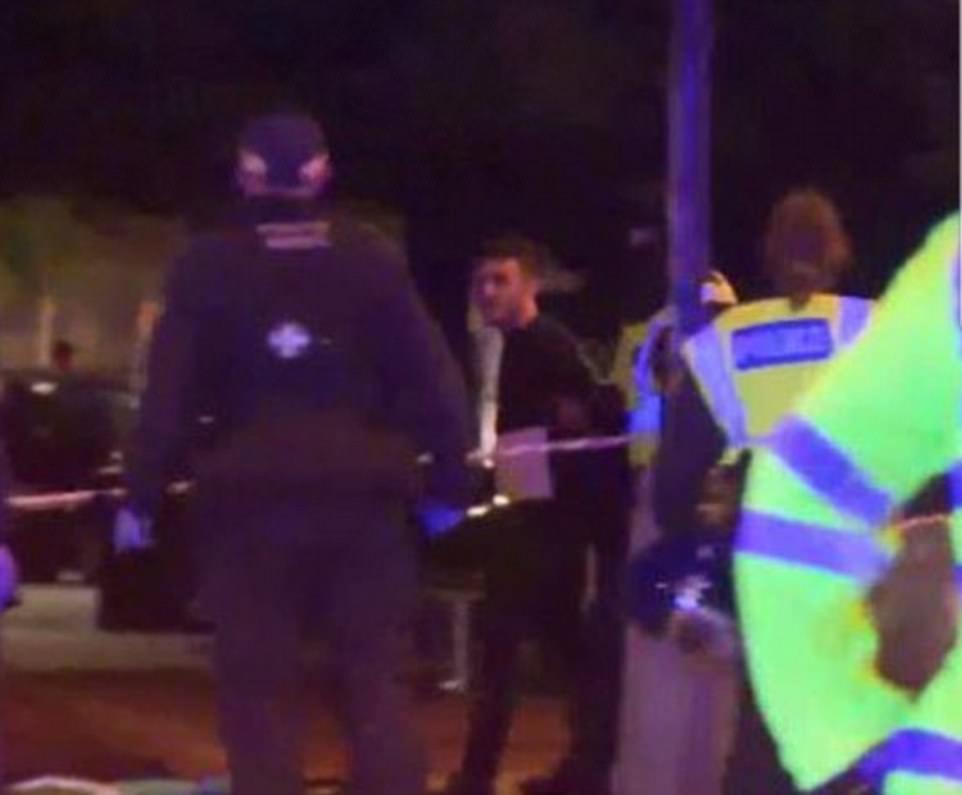 Un hombre en un chándal negro se cree que un sospechoso fue fotografiado siendo detenido por la policía