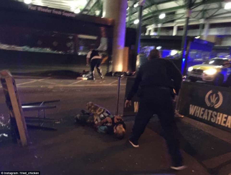 Three Jihadi terrorists were shot dead by armed police after killing seven people and injuring at least 48 more during a horrific knife rampage in central London last night. This photo appears to show the suspects lying dead on the ground outside Wheatsheaf pub in Borough Market. The man in the centre of the image appears to be wearing an Arsenal football shirt