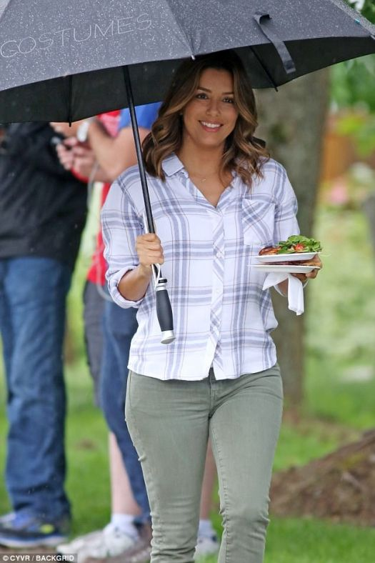 Brolly good show: Eva, 42, juggled an umbrella and two plates of food as she walked across the outdoor set on Monday