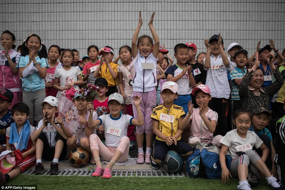 Protecting the Supreme Leader: School children cheer as others take part in sports games marking 'Children's Union Foundation day'