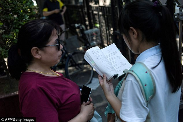 A student reads from her textbook ahead of going into the Gaokao examination