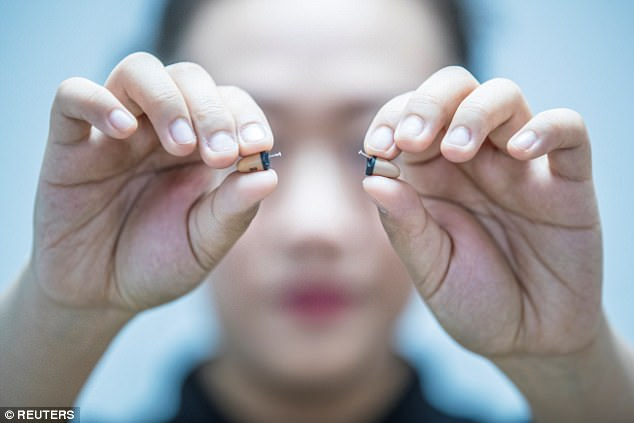 A woman holds a pair of earpieces during a presentation to the meeting in Taiyuan