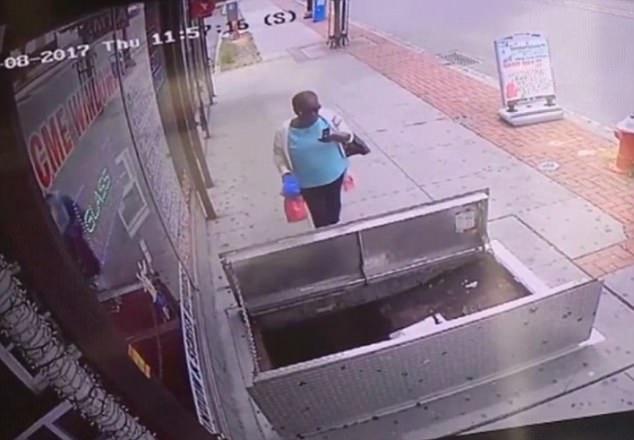 Perempuan tak melihat ada pintu trotoar terbuka