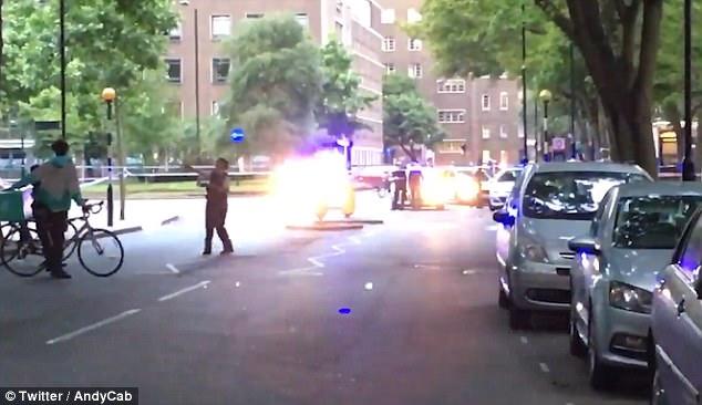 Un oficial de policía dirige un ciclista deliveroo alrededor del cordón después del apuñalamiento