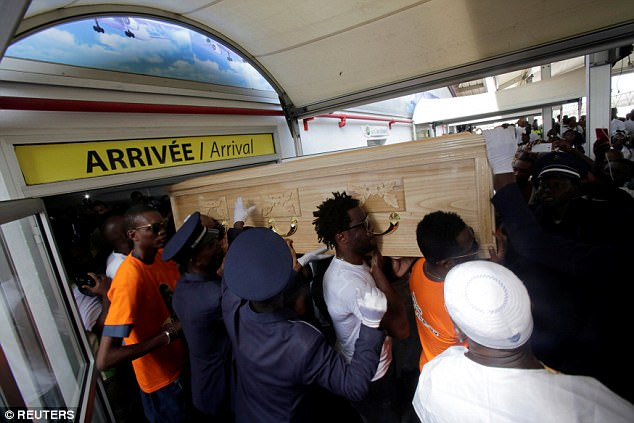 Tiote's casket is carried through arrivals at the Port Bouet airport, the largest in the Ivory Coast
