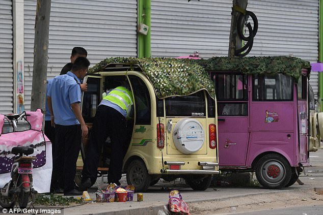 Los agentes de policía verificar los vehículos pequeños fuera un jardín de infancia, donde una explosión golpeó