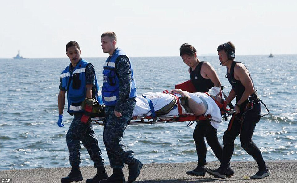 An injured sailor is carried by U.S. military personnel, left, and Japanese Maritime Self-Defense Force members upon arriving at the U.S. Naval base in Yokosuka, southwest of Tokyo