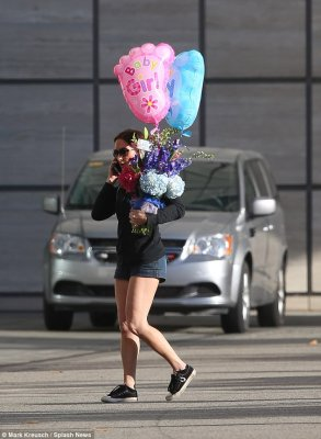 One of each: This rather telling balloon and floral gift was delivered to the hospital on Sunday with a card which read: 'To B and J' following speculation the couple had a boy and a girl