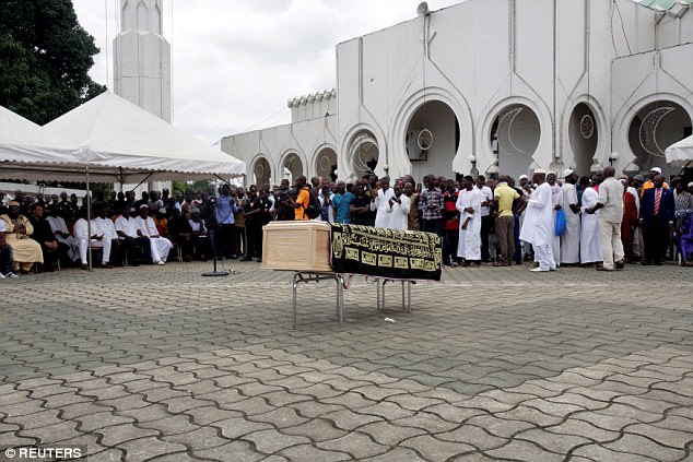 The coffin of Tiote stands in the middle of a square ahead of his funeral service