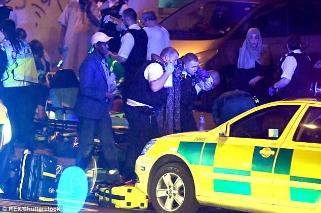 Dos policías ayudan a la víctima hacia un coche de la ambulancia como transeúntes devastadas miran con horror
